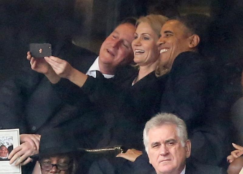 British Prime Minister David Cameron, Danish Prime Minister Helle Thorning-Schmidt and US President Barack Obama pause for a selfie at Nelson Mandela's memorial service in Johannesburg, South Africa. Serbian President Tomislav Nikolic looks on. (Photo credit: vantagenews.co.uk)