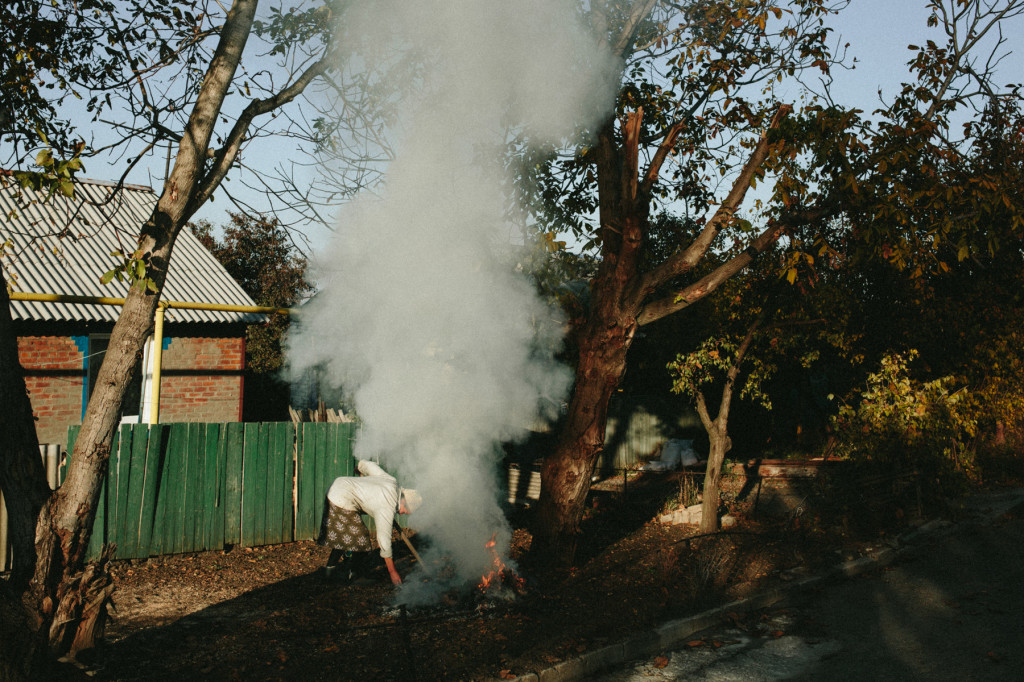 An elderly woman burns autumn leaves in the village of Semonovka, October 2014