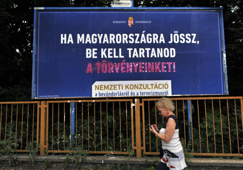 """"""" A woman is walking in front of a vandalized anti immigration billboard reading """"If you come to Hungary, you have to respect our laws!"""" in Budapest, Hungary, on June 15, 2015. Hungary's central-right government has launched a controversial billboard campaign against immigration while UNHCR introduced its counter campaign highlighting successful refugee stories."""" Photo Credit: AP Photo/Bela Szandelszky"""