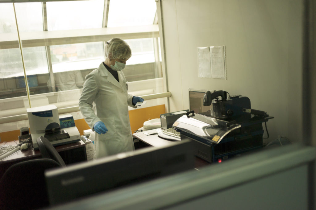 A lab technician prepared blood from living relatives for DNA matching. (Photo credit: Chris Bobyn)