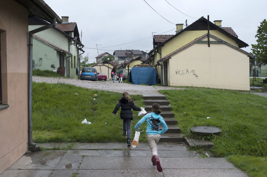 Children run through the pre-fab UNHCR houses in the town of Mihatovići, home to approximately 10,000 Bosnian refugees, a majority from Srebrenica. (Photo credit: Chris Bobyn)